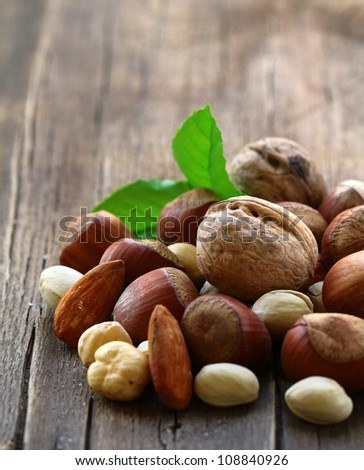 mix nuts - walnuts, hazelnuts, almonds on a wooden table - stock photo