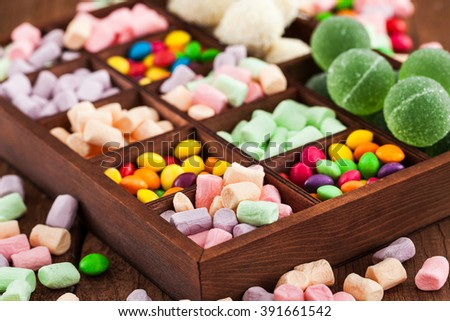 Mix of candies and sweets in wooden printers box - marshmallows, candies, dragee, fruit jelly  - stock photo