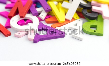 Mix of colorful wooden alphabetical letters. Slightly defocused and close-up shot. Copy space. - stock photo