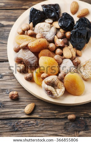 Mix of dried fruits and nuts on the wooden table, selective focus - stock photo