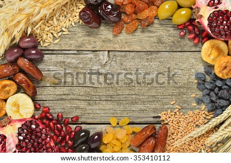 Mix of dried fruits, barley, wheat, olives, pomegranate on wooden table - symbols of judaic holiday Tu Bishvat. Copyspace background.Top view. - stock photo