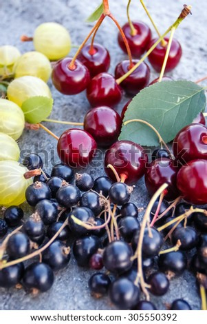 Mix of fresh and juicy cherries, black currant and gooseberries in the summer garden on a grey stone  - stock photo
