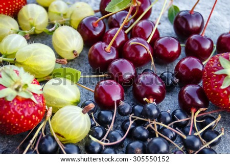 Mix of fresh and juicy cherries, black currant, strawberries and gooseberries in the summer garden on a grey stone  - stock photo