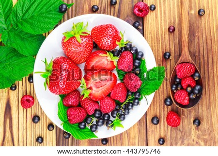 Mix of fresh and ripe berries in plate and spoon on wooden background, top view - stock photo