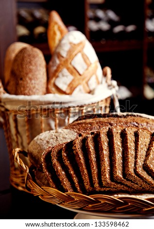 Mix of fresh bread in basket on black background - stock photo
