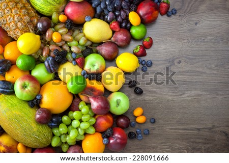 Mix of Fresh Fruits  on dark wooden table with copy space  - stock photo