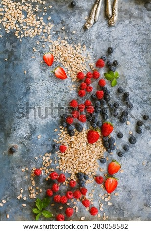 Mix of Fresh ripe berries , blueberry, raspberry and cereals scattered of the blue table. Breakfast food concept. Rustic style. - stock photo