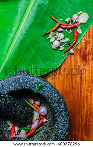 Mix of garlic, chili  and herbs in a mortar ( Top view), wood  background