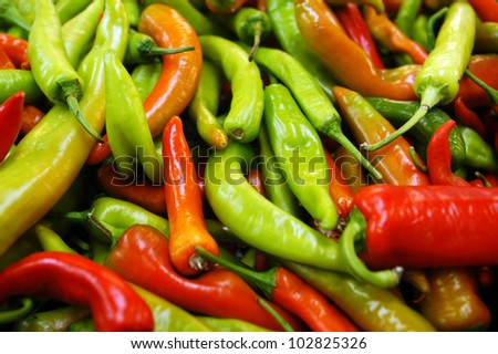 Mix of hot red and green chilies on display in a food Market. - stock photo