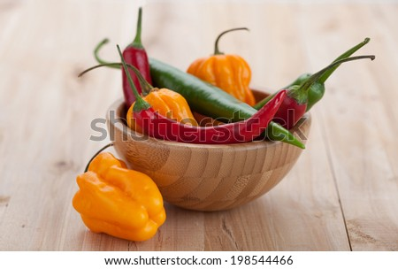 Mix of hottest peppers in wooden plate on table - stock photo