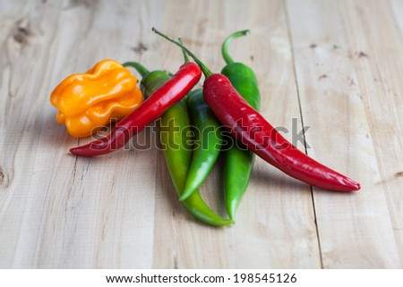mix of hottest peppers on wooden table - stock photo