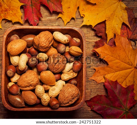 mix of nuts in wooden box with autumn colorful leaves - stock photo
