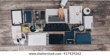 Mix of office supplies and gadgets on a wooden desk