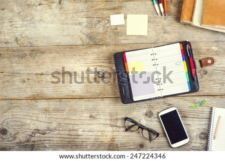 Mix of office supplies and gadgets on a wooden table background. View from above. - stock photo