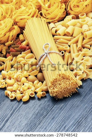 Mix of pasta on wood background - stock photo