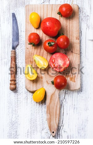 Mix of red and yellow cherry tomatoes on cutting board and vintage knife over white wooden table. See series. Top view. - stock photo