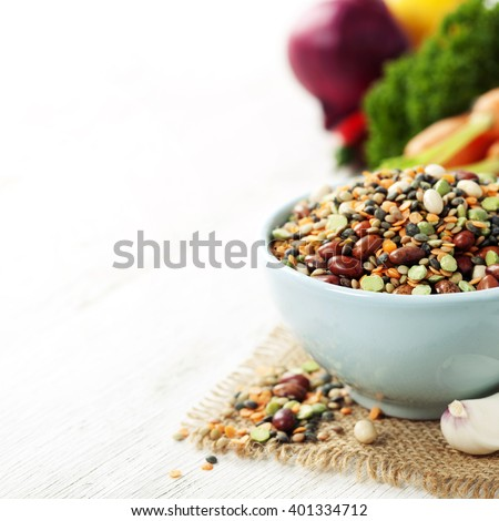 Mix of red  bean, lentil, green peas and chickpeas with vegetables over white - stock photo