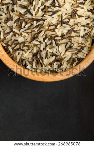 Mix of rice in a wooden bowl on a black background - stock photo