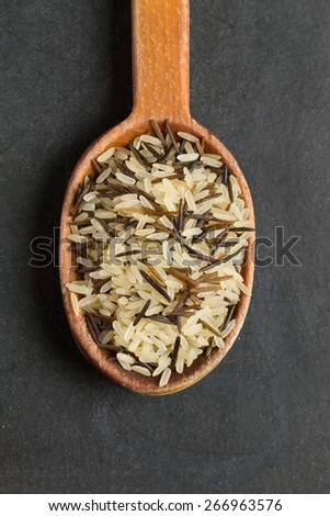Mix of rice in an old wooden spoon on a black background - stock photo
