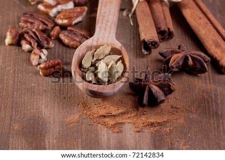 mix of spice cinnamon, anise, pekan, cardamom in wooden spoon on wooden table