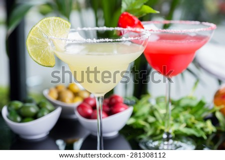 mix of the bright refreshing cocktails lime and strawberry daiquiri on a table in a restaurant with decoration of salt on the edge of the glass with fresh mint and lime slices and berries. soft focus - stock photo