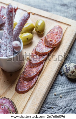 mix of traditional spanish ham salami parma ham on grissini bread sticks, marinated vegetables and olives on wooden plate with rustic decor - stock photo