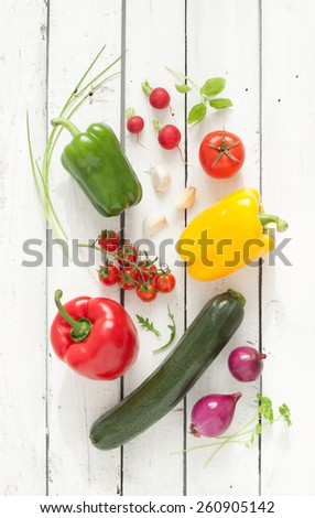 Mix of Vegetables on white planked wood background - summer garden harvest. Red, yellow and green pepper, tomatoes, red onion, zucchini, radish, garlic and herbs from above. - stock photo