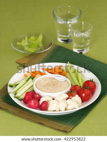 Mix of vegetables radish, carrot, cucumber, celery, cauliflower, tomatoes with sauce on a white plate - stock photo