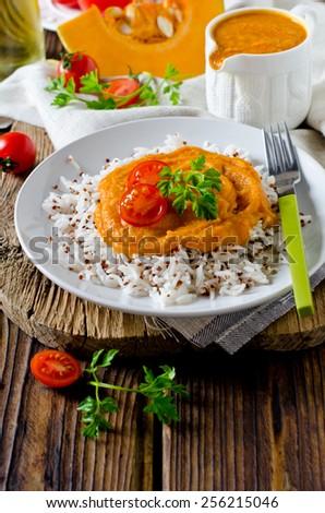 Mix rice and quinoa with pumpkin sauce - stock photo
