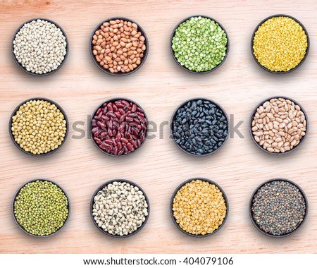 Mixed beans and lentils in bowl on wooden background. - stock photo