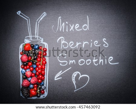 Mixed Berries Smoothie lettering. Various  fresh berries and painted Bottle with drinking straw and heart on blackboard background.  - stock photo