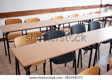 Mixed chairs next to wooden tables in a classroom in Poland - stock photo