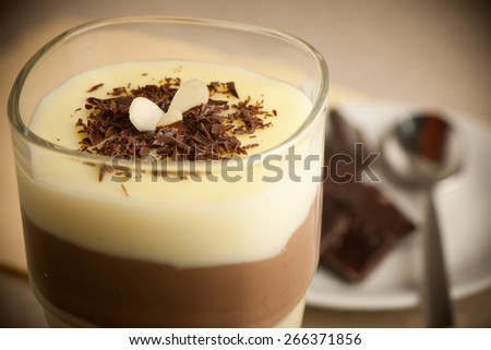 Mixed chocolate and vanilla pudding served in a glass decorated  - stock photo