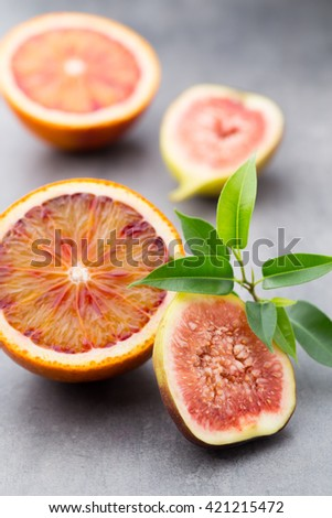 Mixed citrus fruit orange and figs on a gray background. - stock photo