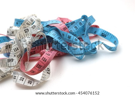 mixed color (blue,pink and white) of measuring tape on a white background, centimeters and inches
