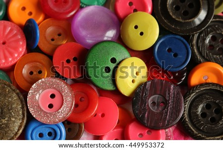 Mixed color bright buttons filling the frame as background.Sewing accessories. - stock photo