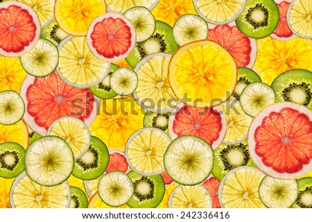 mixed colorful sliced fruits  as background back lighted - stock photo