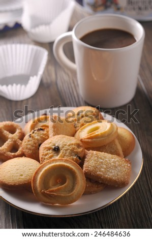 Mixed cookies and black coffee cup on wooden background