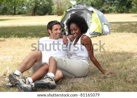 mixed couple camping - stock photo