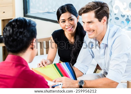 Mixed couple in furniture store with shop assistant discussing colors and material of items they are buying - stock photo