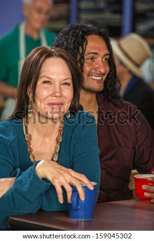 Mixed couple together in cafe with coffee mugs - stock photo