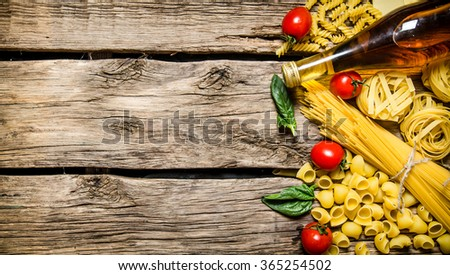 Mixed dry pasta and spaghetti, with tomatoes, herbs and olive oil. On wooden background. Free space for text . Top view - stock photo