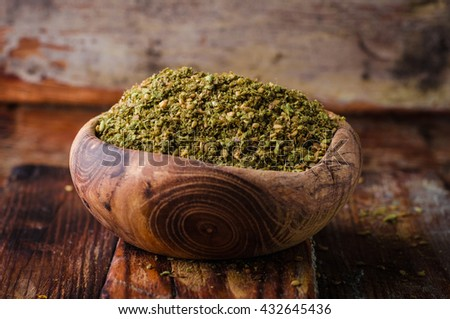 Mixed east spice - zaatar or zatar in vintage bowl on wooden background. Selective focus - stock photo