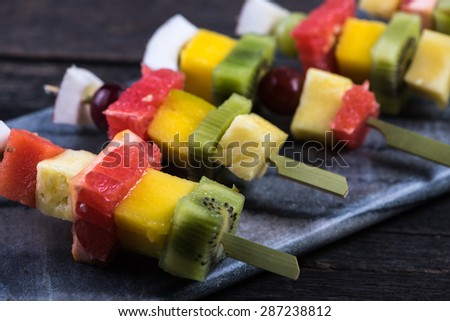 Mixed exotic fruits on skewers, party healthy snack - stock photo