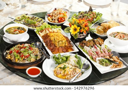 mixed food, full rounded table of Chinese Thai food, duck and sauce - stock photo