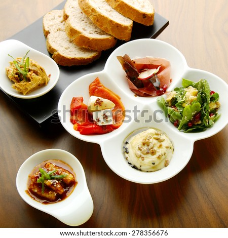 Mixed food on a white and a black plate with ham, yellow dressing, chicken in spicy sauce with sesame seeds and paprika on which pieces of cheese, mint and parsley - stock photo