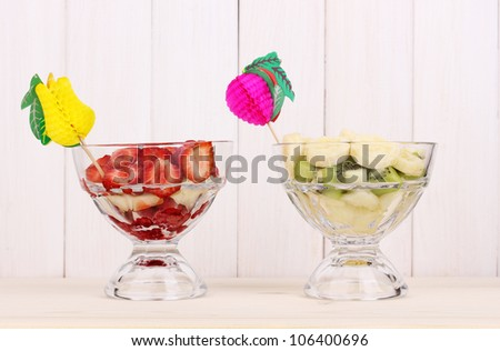 Mixed fruits and berries in glasses on wooden background - stock photo