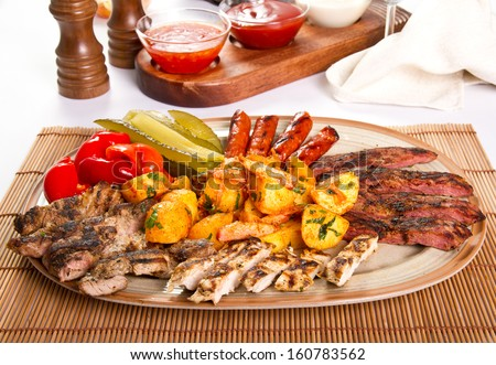 Mixed grilled meat platter and pickles - stock photo