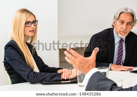 Mixed group in business meeting with notepad, smartphone and water glasses - focus on attractive business woman listening to her opposite with older businessman sitting next to her - stock photo