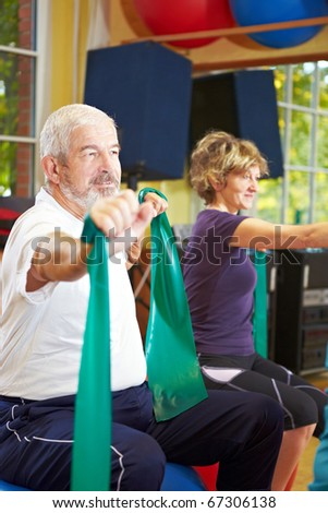 Mixed group in gym exercising with latex band - stock photo